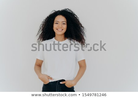 Isolated shot of young African American woman wears white t shirt, expresses good emotions, stands a Stock photo © vkstudio