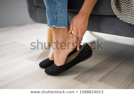Woman's Hand Removing Uncomfortable Ballerinas Stock photo © AndreyPopov