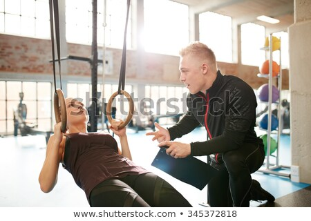 Personal trainer assisting during exercise in sports gym Stock photo © Elnur