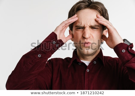 Image of unhappy young man with headache rubbing his forehead Stock photo © deandrobot