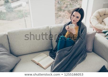 Woman sitting on cosy sofa with mug of coffee Stock photo © photography33
