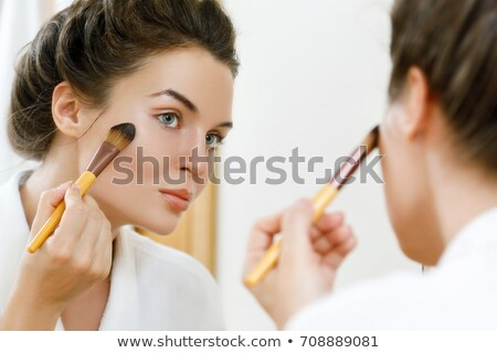 Girl Applying Blusher And Looking In Her Mirror Stock photo © stuartmiles