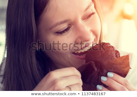 Caucasian woman is eating a muffin  Stock photo © wavebreak_media