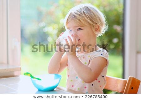 dziewczynka · pitnej · mleka · butelki · płytki · dziedzinie - zdjęcia stock © lunamarina