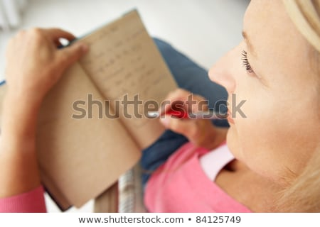 Attractive blonde woman writing in the home. Stock photo © justinb