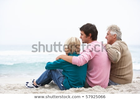 grandfather father and grandson sitting on winter beach stock photo © monkey_business
