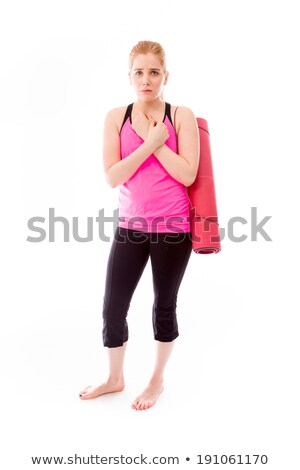 Young woman carrying exercising mat shivering in cold stock photo © bmonteny