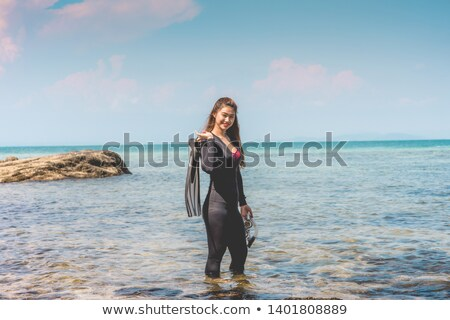 Woman in bikini holding diving equipment at seashore Stock photo © AndreyPopov