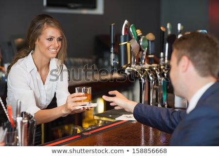 Stock photo: Young waitress with beer on white