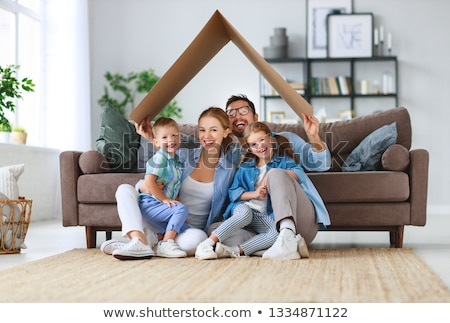 happy family of mother father and daughters sitting on a sofa a stock photo © dashapetrenko