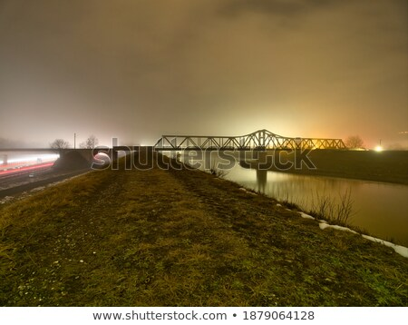 Nightly railroad bridge and calm water Stock photo © Mps197
