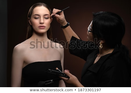 female makeup artist applying professional brush for eyes of woman stock photo © deandrobot