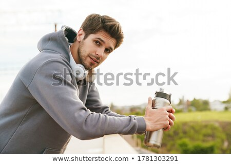 Young sportsman drinking water while leaning on the railing Stock photo © deandrobot