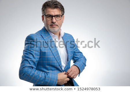 elegant business man buttoning his suit while sitting stock photo © feedough