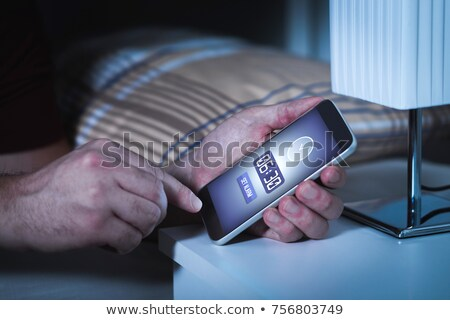 alarming cellphone next to bed stock photo © albund