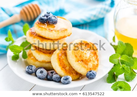 Cottage cheese pancakes with honey and blueberry on white background, breakfast or lunch Stock photo © yelenayemchuk