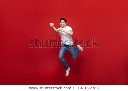 Full length portrait of a confident happy man pointing finger stock photo © deandrobot