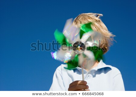 Boy holding pinwheel in front of face Stock photo © IS2
