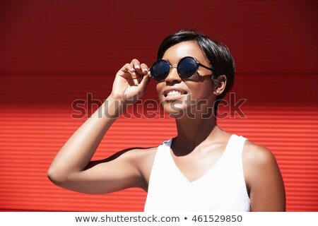 Lovely young woman trying on new sunglasses Stock photo © deandrobot