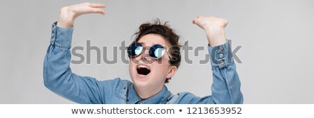 Young brunette girl in round glasses. Hairs are gathered in a bun. The girl lifted her hand up. Stock photo © Traimak