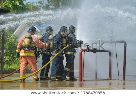 firefighter puts out fire with water from a fire engine Stock photo © studiostoks