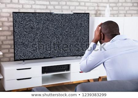 Férfi ül televízió mutat nem jel Stock fotó © AndreyPopov