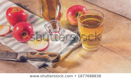 glass of fresh organic apple juice with green apples on wooden background with knife stock photo © denismart