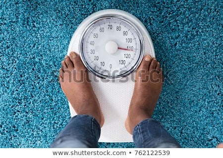 woman standing on weighing scale indicating overweight stock photo © andreypopov