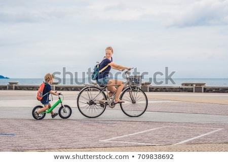 Stockfoto: Happy Family Is Riding Bikes Outdoors And Smiling Mom On A Bike And Son On A Balancebike