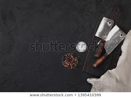 Stock photo: Vintage meat knife and fork and hatchets with vintage chopping board and black table background. But