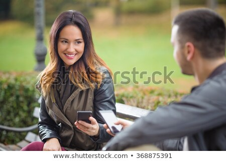 Cute loving couple sitting outdoors while using mobile phones. Stock photo © deandrobot