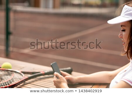 Young female tennis player messaging in her smartphone Stock photo © pressmaster