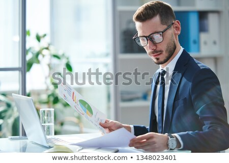 Jovem analista olhando financeiro documentos gráficos Foto stock © pressmaster