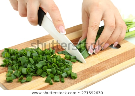 Stock photo: Close up of woman hand cutting salad on chopping wood board with