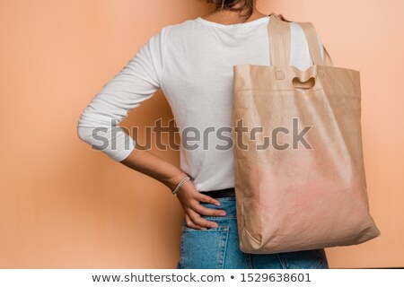 Rear view of young casual woman holding pinkish textile tote bag on shoulder Stock photo © pressmaster