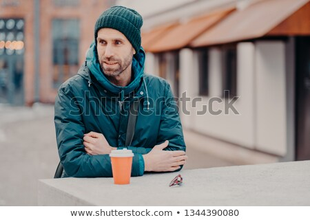Pensive unshaven young Caucasian man with bristle, wears hat and jacket with hoody, drinks takeaway  Stock photo © vkstudio