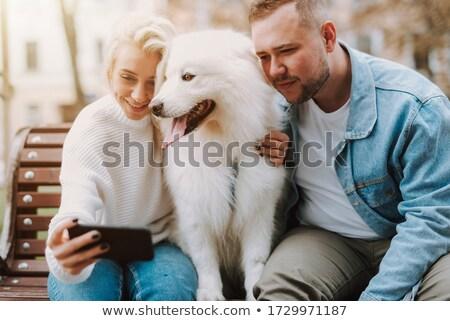 Loving couple with dog samoyed outdoors Stock photo © deandrobot