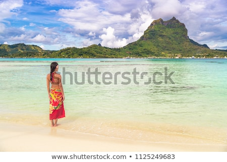 Tahiti luxury travel beach vacation woman walking in polynesian cover-up skirt beachwear on idyllic  Stock photo © Maridav