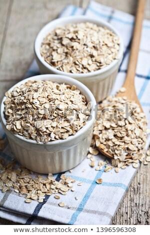 Oat flakes in wooden spoon on linen napkin, golden wheat ears on Stock photo © marylooo