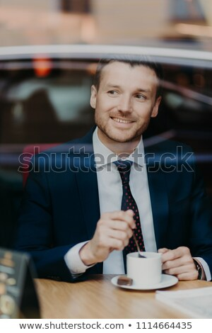 Positive male entrepreneur in formal clothing, drinks coffee, has cheerful expression, looks happily Stock photo © vkstudio