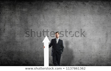 Businessman pointing at sign in his hands against a white background stock photo © wavebreak_media