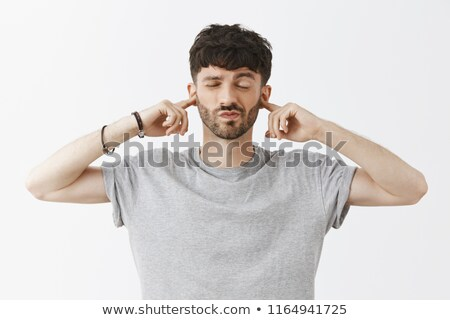 Handsome Man Pointing at Ear Indicating Listening Stock photo © scheriton