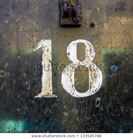 House number eighteen, deteriorated white lettering.  Stock photo © meinzahn