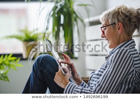 portrait of a young smiling woman with tablet computer at home stock photo © deandrobot