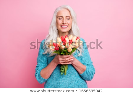 beautiful woman smelling flowers over gray background stock photo © deandrobot
