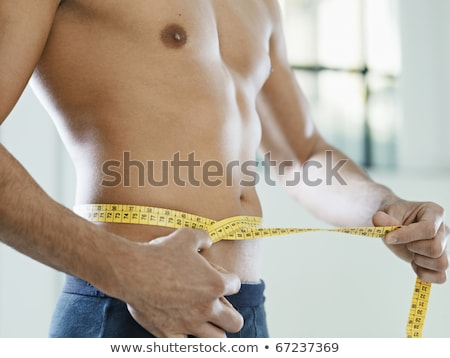 Mid section of a muscular man measuring waist Stock photo © wavebreak_media