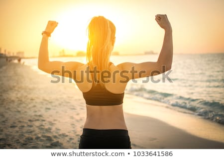 Young sportswoman showing biceps with weights Stock photo © deandrobot