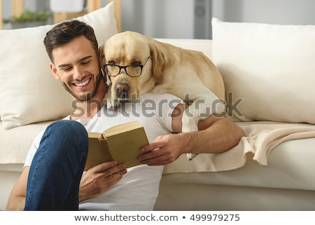 Handsome boy with beard in glasses reading book Stock photo © deandrobot