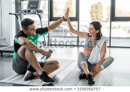Glimlachend aantrekkelijke vrouw atleet drinkwater gymnasium permanente Stockfoto © deandrobot