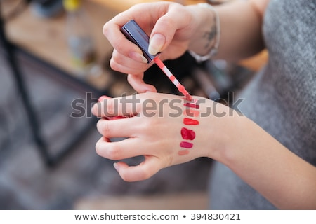 Young female visagiste applying red lipstick to lips of woman  Stock photo © deandrobot